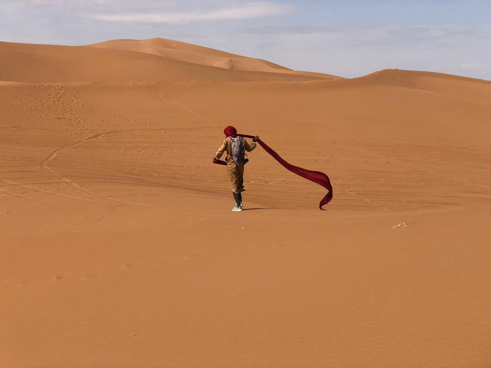 A man walking in the Erg Chebbi sand dunes with a scarf flying behind him.
